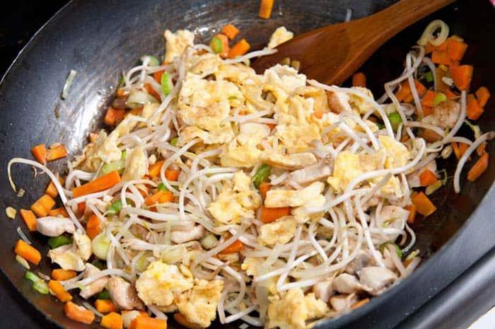 haciendo arroz chino en wok con huevos, pollo y verdura