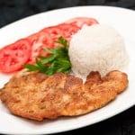 plato de milanesa de pollo con arroz y tomates