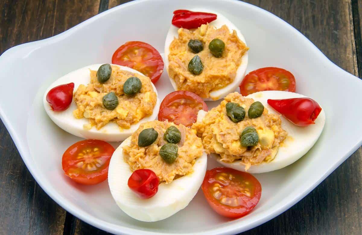 plato con huevos rellenos de atún decoradoc con alcaparras y tomates